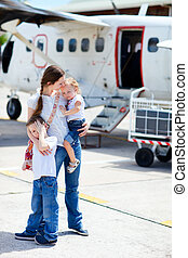 Mother and kids in front of airplane - Young mother with her...