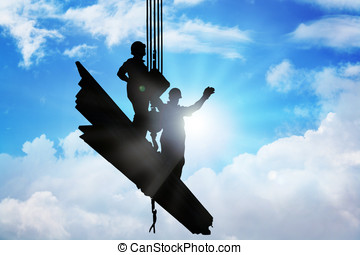 Mega Crane - Two men standing on iron bars held up by mega...