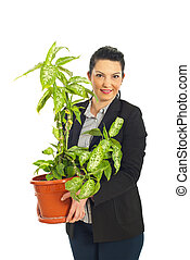 Business woman holding vase with plant - Business woman...