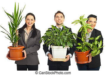 Happy business people holding vases with plants - Happy...