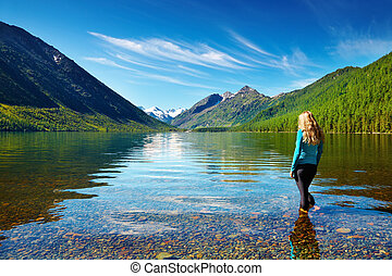 Mountain lake - Mountain landscape with girl standing in the...