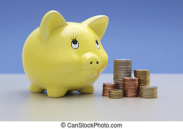 Yellow Piggy bank with stacks of co