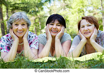 Summer rest - Portrait of three aged women resting on grass...
