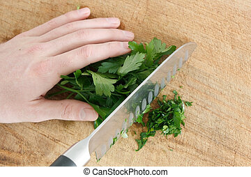 Parsley - Chopping parsley on a wooden surface
