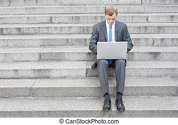 Business man sitting on stairs outdoor