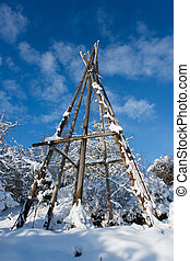 tepee - snowy framework of a tepee tent under blue sky