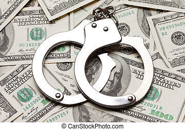 Handcuffs on dollar currency - Crime law handcuffs arrests...
