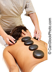 Hot stone massage - Massage in spa room, isolated