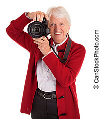 Senior Female Photographer Shooting You - A senior woman is...
