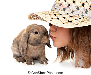 Girl in a straw hat kisses dwarf rabbit. In the Oriental...