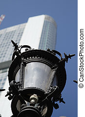 Old lantern in front of a modern office building in...