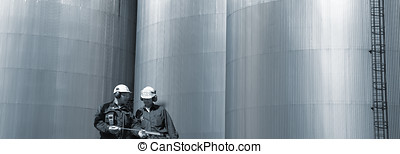 oil and gas engineering - two workers in front of refinery...