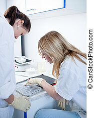 two female researchers doing research in a lab color toned...