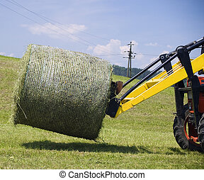 Tractor working with a Hay Bale - Detail view of a Tractor...