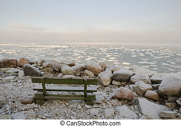 Bench on coast. Winter morning at the sea