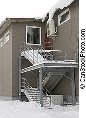Ladder in snow on the second floor with windows