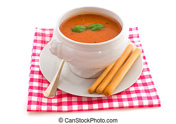 Tomato soup with basil and bread sticks isolated over white...