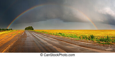 Rainbow over road - Landscape with country road and rainbow