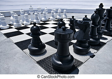 Outdoor playing Chess with big black and white figures