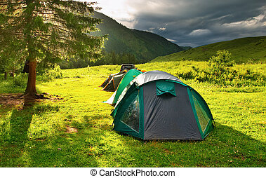 Tourist tents on the glade at sunset