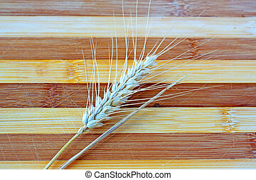 Ear of wheat over a wooden background