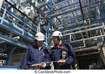 oil-workers inside oil industry - two engineers walking with...