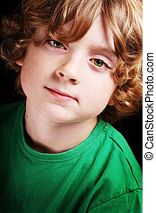 Cute young boy - A cute young boy looking to the camera on a...