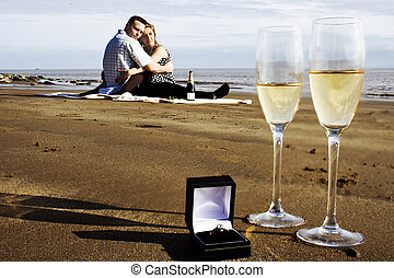 happy couple and champagne glasses with engagement ring -...