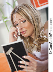 crying woman looking at framed picture - crying blond woman...