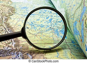 book with maps and magnifying glass - map of the area and a...
