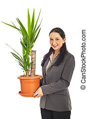 Woman holding vase with Yucca plant - Business woman holding...