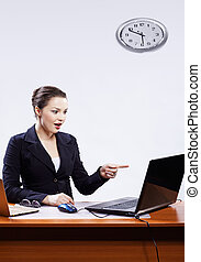 businesswoman with two laptops - office portrait of...