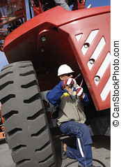 mechanic working oin giant tire - mechanic with giant truck...