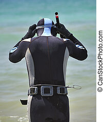 male diver with harpoon on the sea