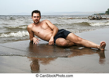 young man lying on lonely wild beach