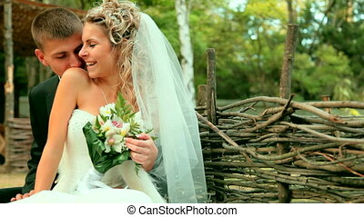 bride and groom on a park bench - bride and groom kiss while...