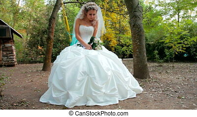 bride on a swing in the autumn park - Bride sits on a swing...