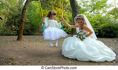 bride with small angel on a swing