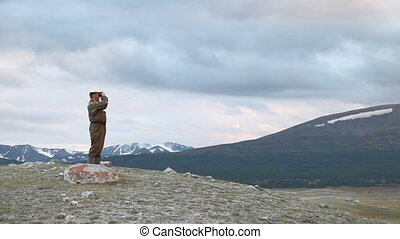 Hiker in mountain look into binocul