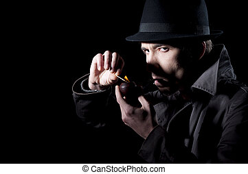 Mistery man - Private detective lighting his pipe, isolated...