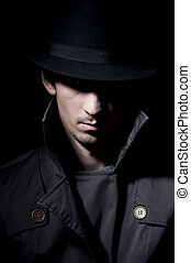 Criminal - young criminal in shadow, isolated on a black...