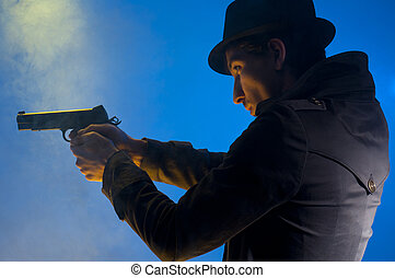 Armed Man - Man holding a gun, shooted in studio on a blue...