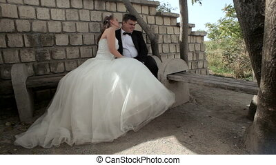 Romantic moment - Newlyweds sitting on the bench and hugging...