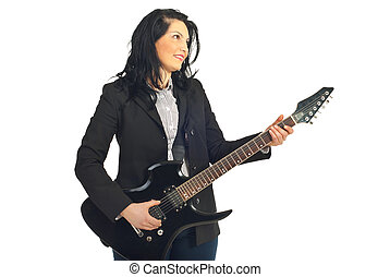 Smiling business woman playing guitar and looking away...
