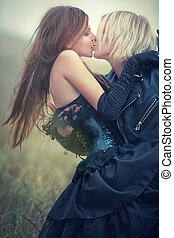 Young goth couple kissing outdoors. Soft colors.