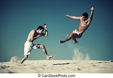 Two young men sport fighting on beach Yellow and blue...