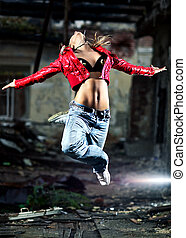 Young woman dancing on industrial background