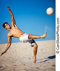 Young man playing soccer on beach Focus on face