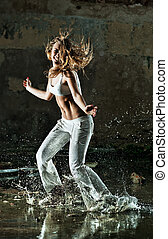 Young woman dancing on street with water