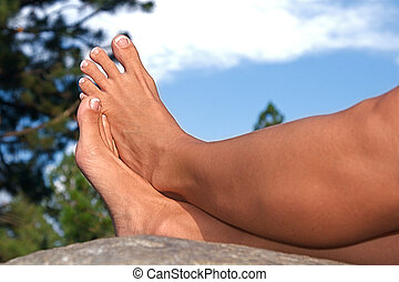 Barefoot on a Rock - Relaxed feet of a woman laying on a...